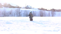 Little boy in a winter cap playing in the snow Stock Footage