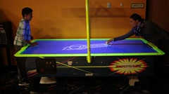 Kids Play Air Hockey at Amusement Park Stock Video - stock footage