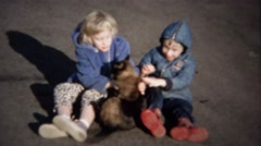 1963: Kids bother cat with rough play runs away for safer times. Stock Footage