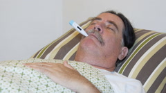 Close-up of sick man in bed with fever and thermometer. - stock footage