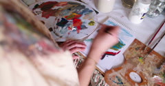Artist painting on paper on a messy studio table - stock footage