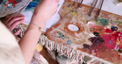 Artist painting on paper with a palette and bright colors Stock Footage
