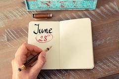 June 28th Calendar Day handwritten on notebook - stock photo