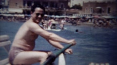 1954: Man rowing Italian novelty leisure boat windy ocean waves. Stock Footage