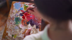 Artist holding palette and mixing colorful paint with paintbrush - stock footage