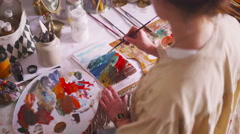 Artist painting on paper with a palette and bright colors - stock footage