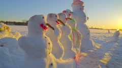 Five snowman aligned on the ground - stock footage