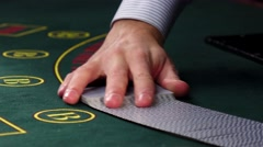 Stock Video Footage of Croupier mixing cards, shows one on green table at casino