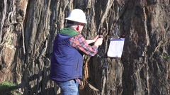 Mining geologist inspecting cliff face for minerals, Mineral wealth Stock Footage