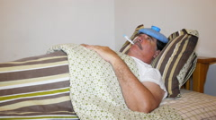 Man sick in bed with fever and head ice bag. Stock Footage