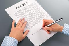 Female hand signs loan contract. Stock Photos