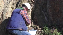 Mining geologist inspecting cliff face for minerals, Mining claim Stock Footage