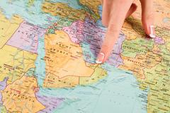 Woman's finger points at UAE. - stock photo