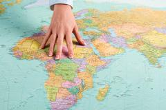 Female hand shows African continent. Stock Photos