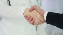 Grateful patient and qualified doctor handshake, healthcare services at clinic Stock Footage