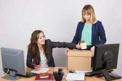Office employee happily helps collect things sacked colleague Stock Photos