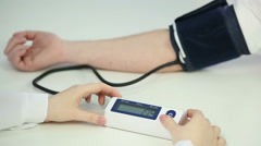Woman doctor checking patient's blood pressure using sensor, health monitoring Arkistovideo