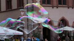 Man creates huge long soap bubbles, Römerberg square tourist attraction Stock Footage