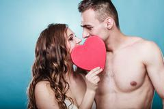 romantic couple kissing behind red heart - stock photo
