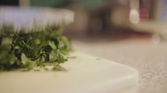 Cutting fresh organic parsley with knife on wooden cutting board. Stock Footage