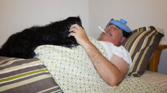 Man sick in bed with his pet dog giving him comfort. - stock footage