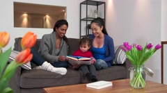 Homosexual Family With Lesbians Women Girls Reading Book To Baby Stock Footage