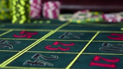 One gambling chip falling down on roulette table, slow motion Stock Footage