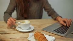 Woman driking coffee and working in coffeeshop. Slow motion - stock footage