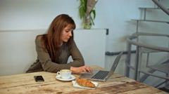 Woman driking coffee and working in coffeeshop. Slow motion Stock Footage