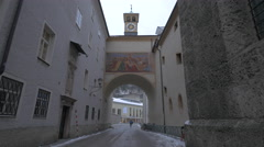 View of a clock tower above an arch with murals in Salzburg Stock Footage