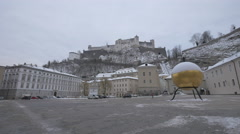 Person running by a big golden ball in Kapiteplatz and Salzburg Fortress Stock Footage