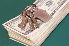 A bundle of banknotes and keys on a green table Stock Photos