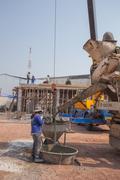 Concrete mixer truck pouring cement at construction site - stock photo