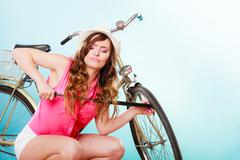 Stock Photo of Woman pumping up tire tyre with bike pump.