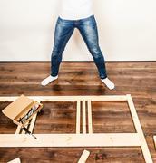 Woman assembling wood furniture. DIY. - stock photo