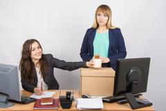 Office worker happily helps collect things sacked colleague - stock photo