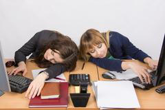 Two young office employee asleep on desk for computers - stock photo