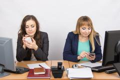 Office workers are engaged in private affairs in mobile phones at his desk Stock Photos