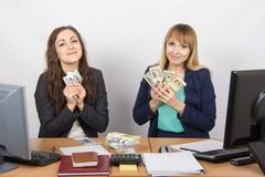 Two girls at the desk office cuddle money packs - stock photo