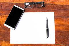 Blank paper with pen and smartphone on wood table concept and Idea for write - stock photo
