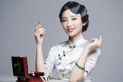 Young beautiful woman in traditional cheongsam with perfume - stock photo