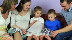 Parents with kids and grandmother consider an album with photos. Happy family Stock Footage