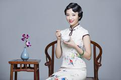 Stock Photo of Young beautiful woman in traditional cheongsam eating porridge