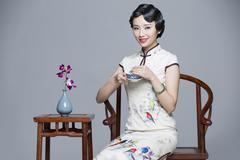 Stock Photo of Young beautiful woman in traditional cheongsam drinking tea