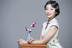 Stock Photo of Young beautiful woman in traditional cheongsam with orchid