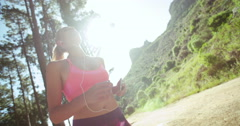 Healthy woman using phone while outdoors ready for a run - stock footage