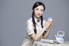 Young beautiful woman in traditional cheongsam drinking tea - stock photo