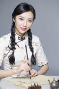Young beautiful woman in traditional cheongsam practicing calligraphy - stock photo