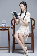Young beautiful woman in traditional cheongsam reading book - stock photo