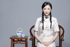 Stock Photo of Young beautiful woman in traditional cheongsam with tea set